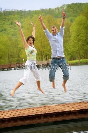 glueckliches paar beim springen am see