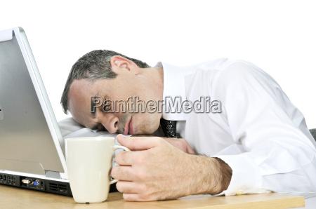geschaeftsmann schlief an seinem schreibtisch auf