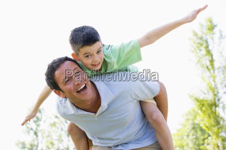 man giving young boy piggyback ride