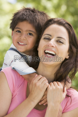 woman and young boy embracing outdoors