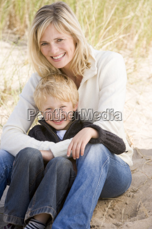 mother and son sitting on beach