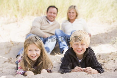 family relaxing on beach smiling