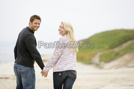 couple walking at beach holding hands