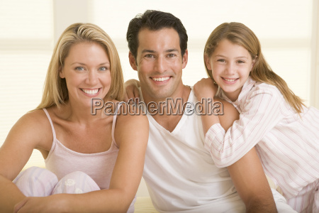 family sitting in bed smiling