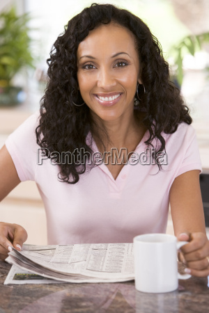 woman in kitchen with newspaper and