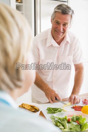 husband talking to wife while preparing