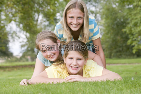 three young girl friends piled on