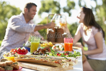 couple dining al fresco toasting each