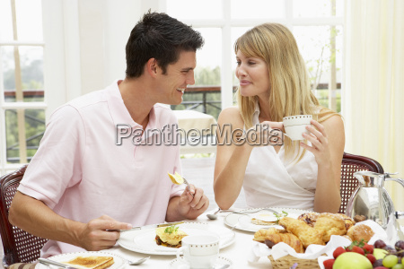 young couple enjoying hotel breakfast