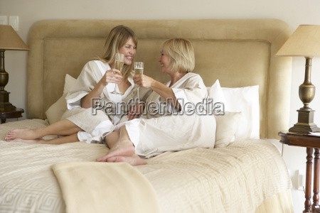 two women enjoying champagne in bedroom
