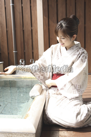japanese woman scooping the hot water
