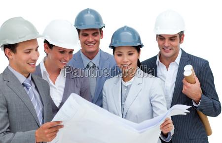 multi ethnic architects studying blueprints
