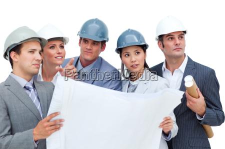 confident architects studying blueprints