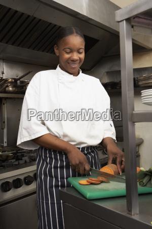 female chef preparing vegetables in restaurant