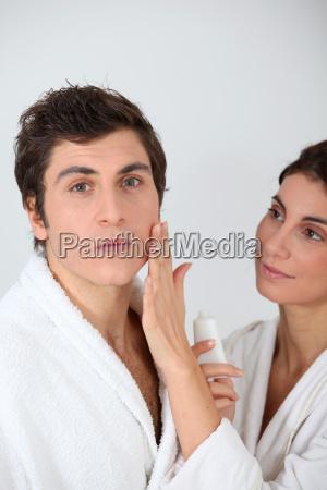 woman applying moisturizer on boyfriends cheek