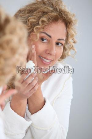 portrait of beautiful woman applying moisturizer