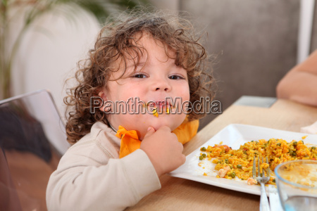 little boy eating rice at kitchen