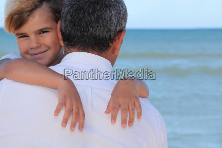 a father hugging his son on