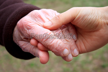 senior and young holding hands