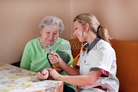 altenpflegerin misst blutdruck bei seniorin
