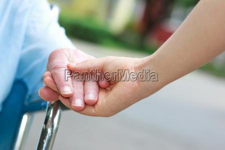senior women in wheelchair holding hands
