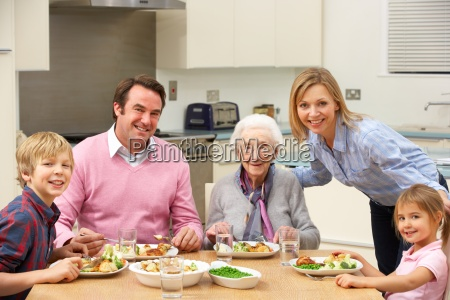 multi generation family sharing meal together