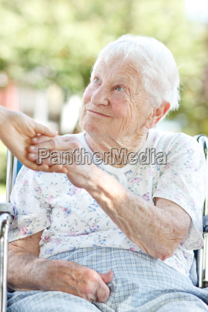 senior woman holding hands with caretaker