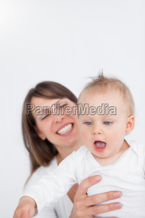 smiling mother holding her surprised baby