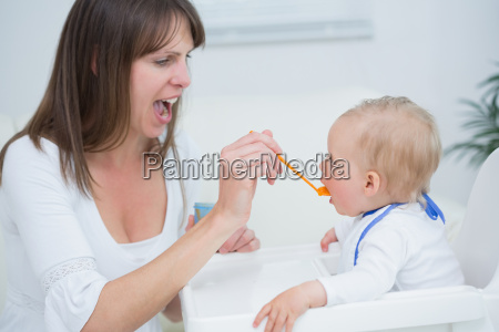 mother feeding a baby while opening
