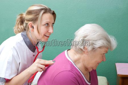 aerztin untersucht patientin mit einem stethoskop