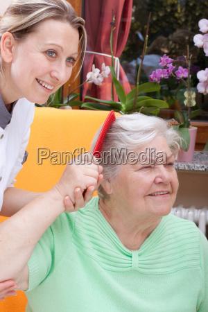 pflegerin kaemmt das haar einer seniorin