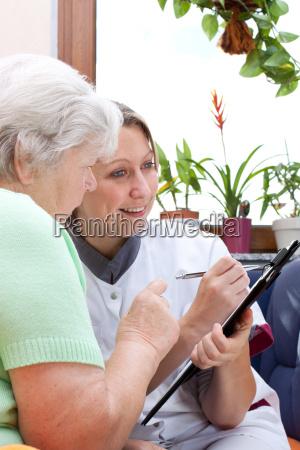 seniorin und pflegerin sitzen zusammen und