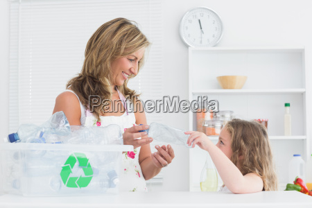 smiling mother sorting waste with her