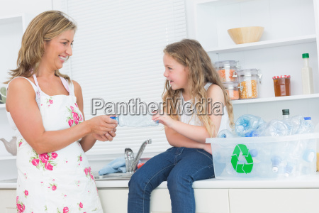 smiling mother sorting plastics waste with
