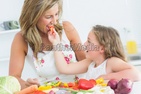 smiling daughter feeding her mother piece