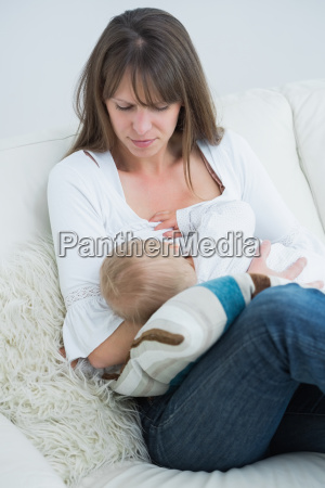 baby having milk from the breast