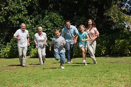 happy multi generation family running towards