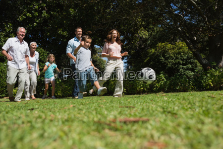 cheerful multi generation family playing football