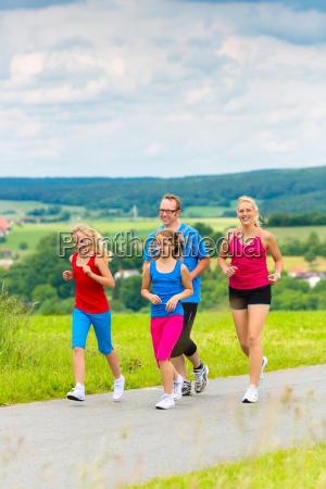 glueckliche familie joggt im sommer