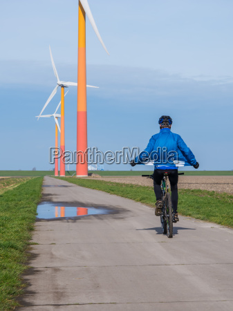 mountain biker riding near wind turbine