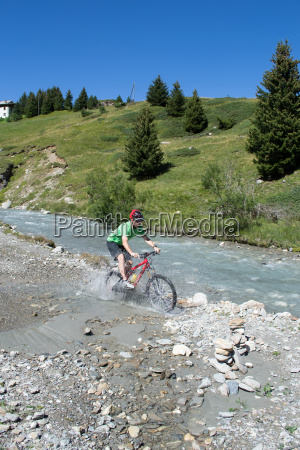 mountain biker riding through stream