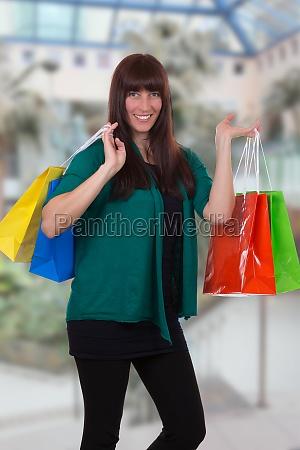 lachende frau beim einkaufen in shopping