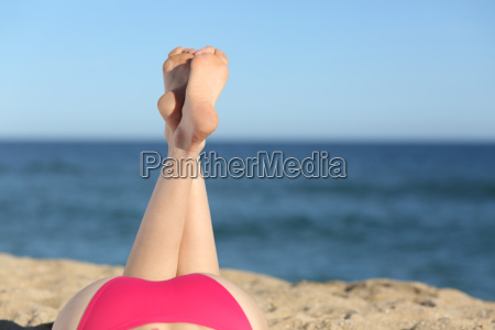 woman legs sunbathing on the beach