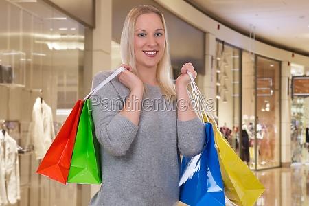 blonde frau beim einkaufen mit einkaufstaschen