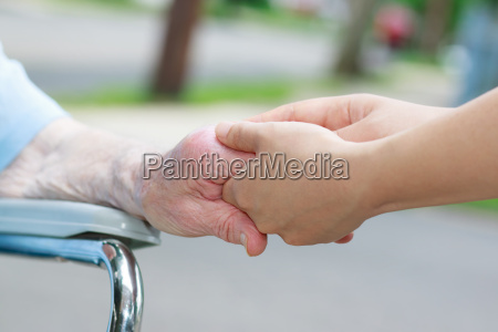 caregiver holding elderly womans hand