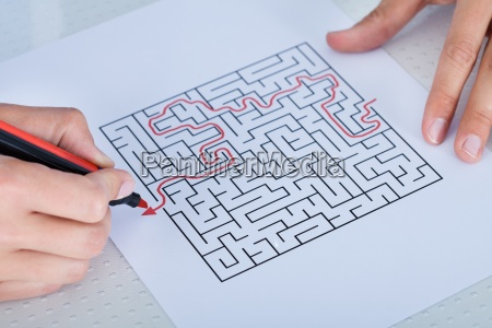 close up of hand solving maze