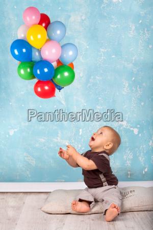 kleiner junge spielt mit luftballons