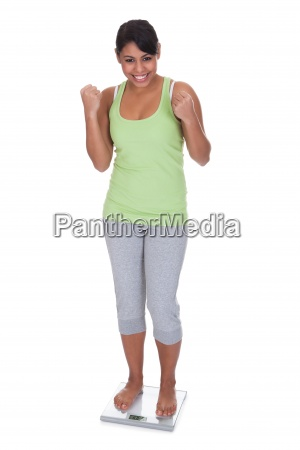 happy woman standing on weighing scale