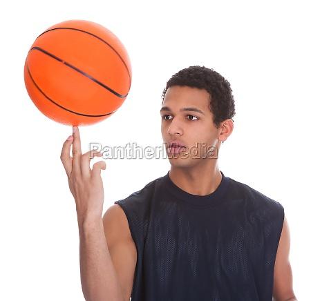 young sportsman balances ball on a