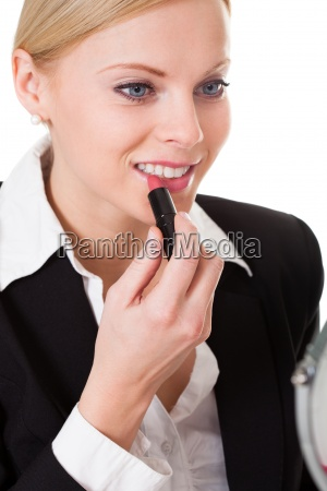 attractive businesswoman applying lipstick